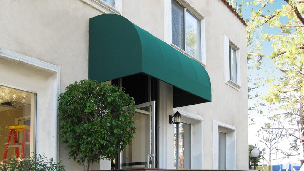 A green convex awning covers the front door