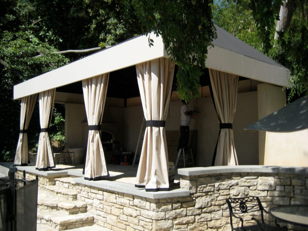 A lovely custom cabana in cream and brown tones that complement the stonework